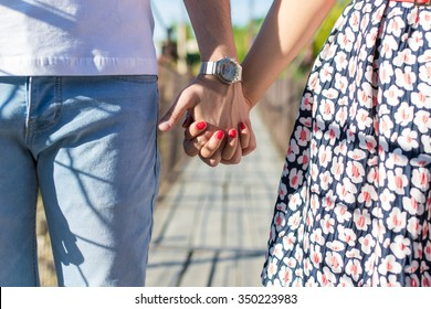 A loving young couple holding hands.