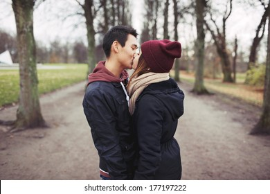 Loving young couple kissing outdoors in the park. Mixed race man and woman. Teenage love.