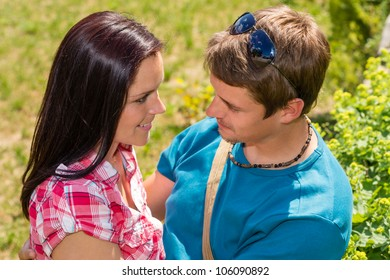 Loving young couple looking at each other in sunny park