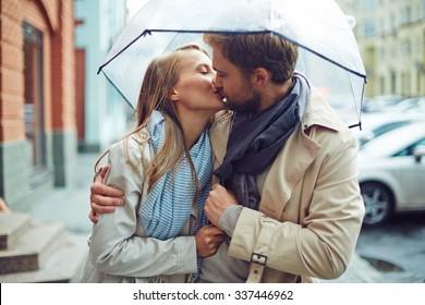 Loving young couple in love under umbrella in the rain