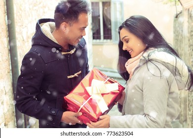 Loving young couple on a date  with a gift outdoor.Christmas concept