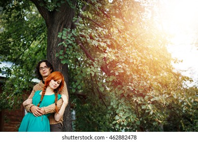 Loving young couple posing and embracing under green tree outdoor. Sunny summer day.