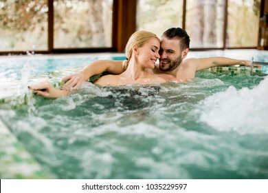 Loving young couple relaxing in hot tub in spa