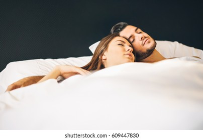 Loving young couple sleeping together in a bed with white sheets at home - Two lovers sleeping under blanket in their bedroom - Life's moment of couple in love