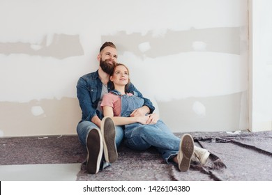 Loving young couple taking a break fro renovations sitting on the floor in an unfinished room in a close embrace looking happily up into the air admiring their work