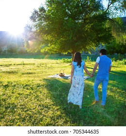 A loving young couple walking in the park and holding hands