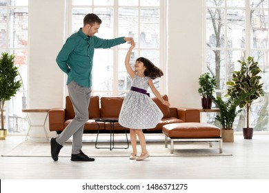 Loving young dad dancing with happy cute little daughter holding hand of kid girl princess wearing dress, caring father teaching waltz small child playing in living room enjoy time together at home