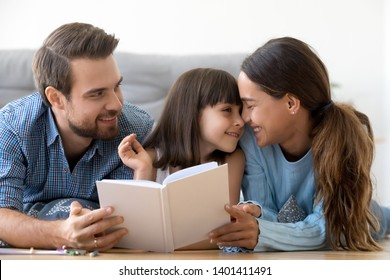 Loving young family with little kid lying on floor in living room reading interesting children book, happy parents enjoy spending time with preschooler daughter, share sweet moments relaxing at home