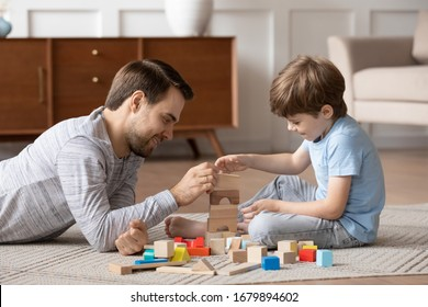 Loving young father lying on floor in living room playing building bricks with little preschoolers son, caring dad relax with small boy child engaged in funny learning activity at home together