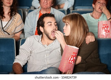 Loving young girlfriend feeds boyfriend popcorn in a theater