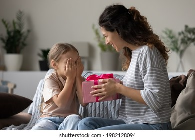 Loving young Hispanic mother congratulate excited small daughter with birthday give wrapped gift. Caring happy Latin mom greeting make surprise with present for little girl child, celebrate together.