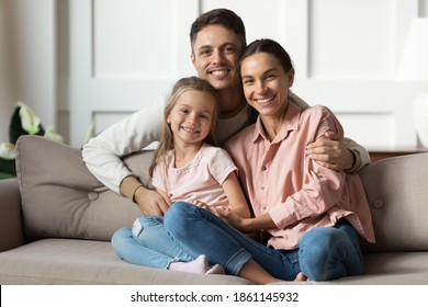 Loving young man hug his beloved wife and little daughter sit on couch in living room, happy people smiling looking at camera posing for photo picture. Exemplary family portrait, love and bond concept