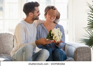 Loving young man sit on couch with happy woman close her eyes, presenting flowers and gift box, caring husband make birthday surprise to amazed wife, congratulating greeting giving bouquet