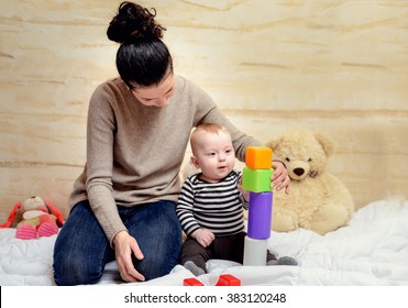 Loving Young Mom and her Cute Baby Boy Playing with Colored Plastic Blocks at Home.