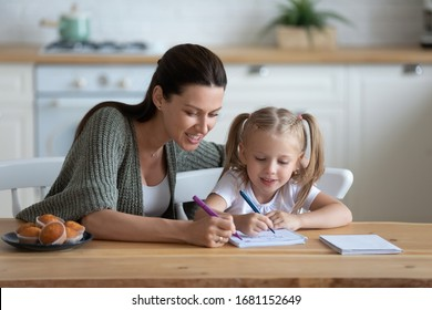 Loving young mother and little preschooler daughter sit at table drawing on paper together, caring mum or nanny playing with small girl child, paint pictures in notebook, early development concept