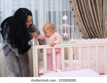Loving young mother teaching her adorable little baby daughter to stand helping her balance in a corner of her cot in the nursery