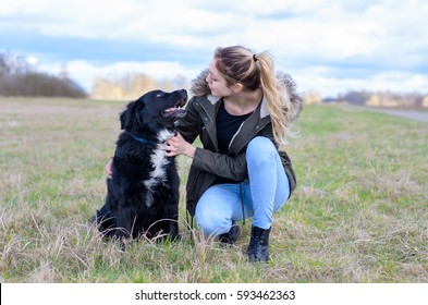 Loving young woman with her loyal black dog crouching down in a field to embrace it as they look into each others eyes with love, close up frontal view
