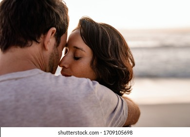 Loving young woman standing with her eyes closed in the arms of her loving husband on a beach at sunset
