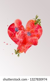 Lovingly designed heart photomontage with raspberries, blackberries, strawberries and water splashes in the background