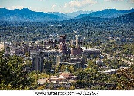 low aerial view of downtown Ashevill, North Carolina and mountains
