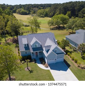 Low aerial view of house with new roof and golf course behind.