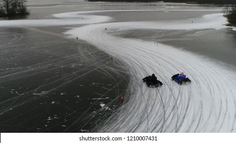 Low altitude aerial photo of go-karts drifting through corners of frozen lake ice track showing the two karts in competition trying to stay ahead then driving away behind tree line