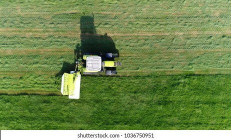 Low altitude aerial top down photo of meadow and farmer in tractor cutting the green grass field after this the cut grass can dry and be picked up so it can be used as animal fodder for cows