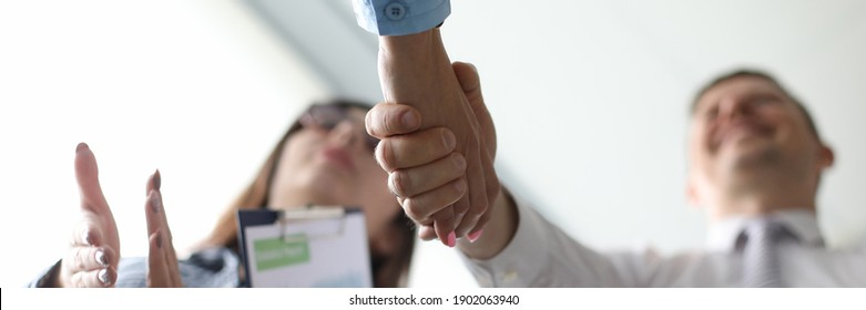 Low angel photo of happy adult businessmen making handshake with his partner with woman next to him. Congratulation and merger concept