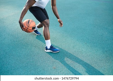 Low angle action shot of African-American man playing basketball outdoors, copy space