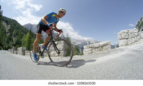 LOW ANGLE: Active young man on road bicycle charging up steep asphalt road in the mountains during a pro bike race. Extreme sportsman training hard for bicycle race in picturesque summer nature.