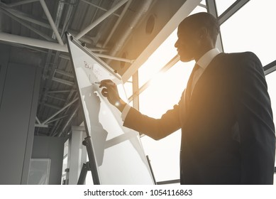 Low angle of african man in suit writing with marker on board. Sun is shining into large window