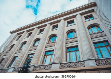 Low Angle Architectural Exterior of Modern Low Rise Building in Classical Style with Large Windows, Decorative Stone Scroll Work and Pillars, Framed Against Blue Sky with Heavy White Clouds