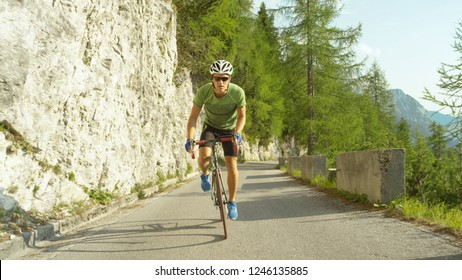 LOW ANGLE: Athletic Caucasian man training for a cyclocross race in the spectacular sunny mountains in Slovenia. Young male road cyclist pedalling his new road bike up a picturesque asphalt route.