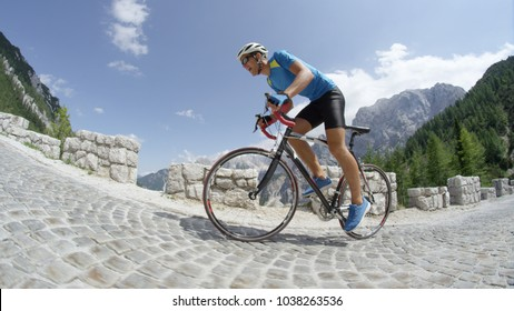 LOW ANGLE: Athletic man rides his bicycle up steep mountain on a sunny day. Breathtaking mountains and cobblestone road host an extreme bicycle race with young man riding his bike with determination.