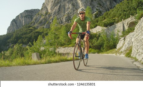 LOW ANGLE: Athletic man riding his road bicycle down the empty asphalt road running through the lush green forest in Slovenian mountains. Young Caucasian road biker speeding downhill on his bicycle.