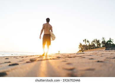 Low angle back view of fit shirtless anonymous male athlete in shorts strolling on sandy beach with footprints near ocean with surfboard in sunlight in evening