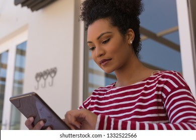 Low angle of a beautiful African American woman using a digital tablet on her terrace at home