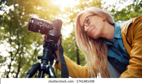 Low angle of blond woman looking at digital camera display taking pictures in green leafy forest