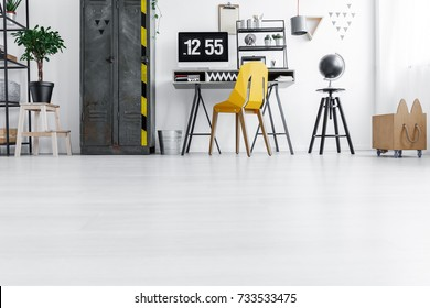 Low angle of bright home office with yellow chair at desk with computer monitor, designer stool and wardrobe