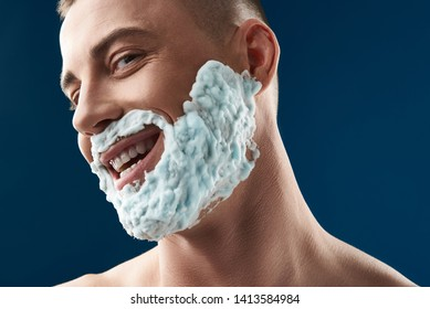 Low angle of Caucasian man with foam for shaving on his face situating against blue background. Male model is smiling while looking at camera. Body care and male hygiene concept