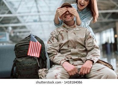 Low angle of cheerful woman situating behind her husband in American military uniform. Wife closed her spouse's eyes with palms indoors. Homecoming concept