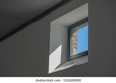 Low angle and close up interior view of square single window with thick new inner white wall, clear transparent glass, black frame and outer old brick wall, and background of deep blue sky.