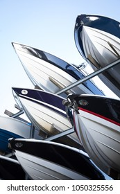 Low angle close up on a rack of modern speedboats for sale, with pointed fiberglass hulls and bows, at a maritime storage dockyard