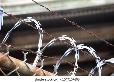 Low angle close up on sharp razor blade points on a coiled row of concertina ribbon and line of rusted barbed wire, ontop of a metal chainlink fence