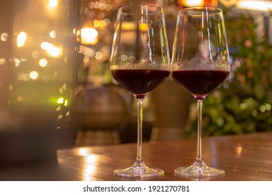 Low angle close up perspective of crystal clear wine glass in warm light background