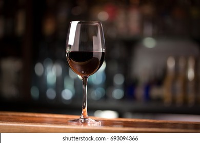 Low angle close up perspective of crystal clear wine glass with traditional round goblet shape filled with dark red wine and slim stem on wood counter top bar with blurry restaurant background scene