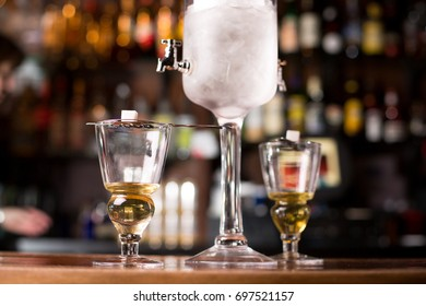 Low angle close up perspective of old fashion absinthe fountain filled with wormwood liquor and ice cubes pouring beverage into two glasses over sugar cube on stainer with blurry bar scene background