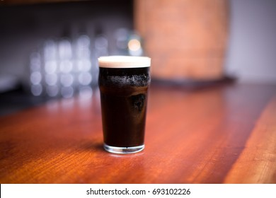 Low angle close up perspective of traditional tumbler pint shape beer glass filled with dark malt stout nitrogen porter with foam head on wood counter top bar with blurry restaurant background