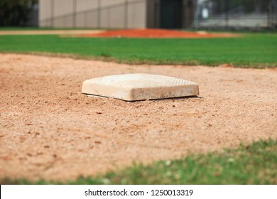 Low angle close up selective focus view of third base on a youth baseball field