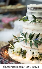 Low angle close up of a three tiered homemade wedding cake with white vanilla crumb frosting and garnished by flowers and laurel leaves, with blurry dessert table background